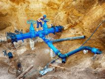 Technical open gate valve on drink water pipes joined with new black waga multi joint members into old pipeline system. Royalty Free Stock Image