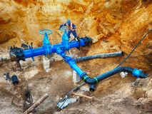 Technical open gate valve on drink water pipes joined with new black waga multi joint members into old pipeline system. Royalty Free Stock Photos
