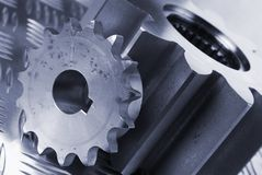 Technical parts in blue. Cogs, gears leaning towards right in blue against patterned steel Royalty Free Stock Photos