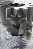 Technical parts idea. Large and smaller gears connecting on patterned stainless-steel Stock Photo