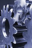 Technical profile of gears. Large gears, cogs connecting with one smaller in a bluish tint Royalty Free Stock Photo