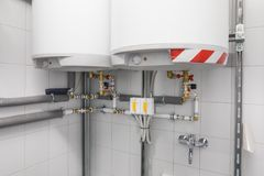 Boiler for water heating, piping system. Technical room for water heating with white boiler and piping system with green and red valves Stock Image