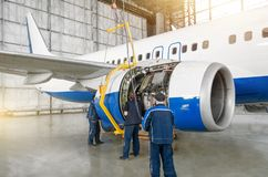 Technical specialists and aircraft mechanics install the reverse engine. Concept maintenance of airplane royalty free stock photography