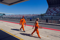 Technical staff male and female in an orange jumpsuit , the clothes are on the inner track Royalty Free Stock Photo