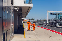 Technical staff male and female in an orange jumpsuit , the clothes are on the inner track Stock Image