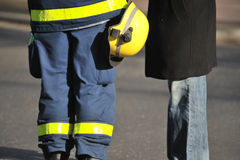 Technical support. Two men standing at the road, one casually dressed, the other wearing technical worker protective clothes with helmet Royalty Free Stock Photography