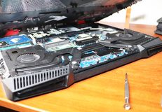 A geek cleans a laptop cooler. Contaminated computer cooling system. stock image