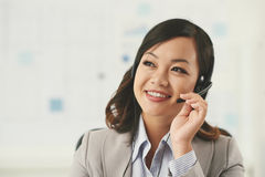 Technical support. Vietnamese smiling technical support manager consulting client Royalty Free Stock Image