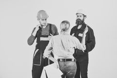 Technical task concept. Brigade of workers, builders in helmets, repairers and lady customer discussing contract, white. Background. Woman customer asks for Royalty Free Stock Photo