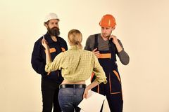 Technical task concept. Brigade of workers, builders in helmets, repairers and lady customer discussing contract, white. Background. Woman customer asks for stock photography