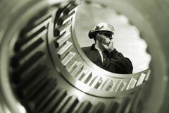 Technical worker and large gears shafts Royalty Free Stock Photo