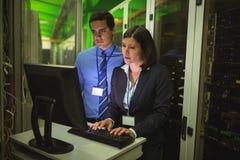 Technici die aan personal computer werken terwijl het analyseren van server royalty-vrije stock fotografie