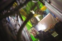 Technici die digitale tablet en laptop met behulp van terwijl het analyseren van server stock afbeelding