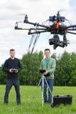 Technici die UAV Helikopter in Park vliegen royalty-vrije stock afbeelding