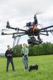 Technici die UAV Spionhommel vliegen royalty-vrije stock afbeeldingen