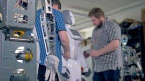 Technici die verscheidene robots in een workshop assembleren stock videobeelden