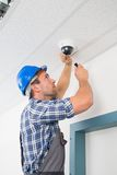 Technician adjusting cctv camera. Close-up Of A Technician Adjusting Cctv Camera On Ceiling Stock Images