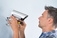 Technician adjusting cctv camera. Close-up Of A Technician Adjusting Cctv Camera On Wall Royalty Free Stock Photo