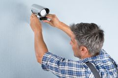 Technician adjusting cctv camera. Close-up Of A Technician Adjusting Cctv Camera On Wall Royalty Free Stock Image