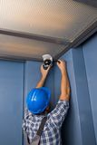 Technician Adjusting Security Camera. Close-up Of Male Technician Adjusting Security Camera On Ceiling Stock Photo