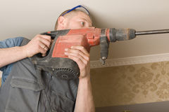 Technician air conditioning drills the wall Stock Photo
