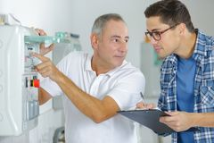 Technician and apprentice fixing photocopier machine. Technician and apprentice fixing a photocopier machine Royalty Free Stock Image