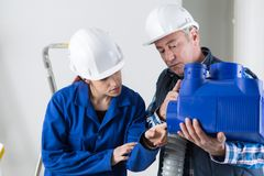 Technician and apprentice working on ventilation pipes stock photos