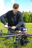 Technician Assembling Propeller Of UAV. Young technician assembling propeller of UAV octocopter in park stock images
