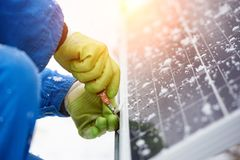 Technician in blue suit installing blue solar panels with screw. Photovoltaic modules as renewable energy source. Alternative energy production innovation Stock Photo