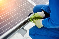 Technician in blue suit installing blue solar panels with screw. Photovoltaic modules as renewable energy source. Alternative energy production innovation Royalty Free Stock Image