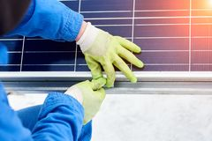 Technician in blue suit installing blue solar panels with screw. Photovoltaic modules as renewable energy source. Alternative energy production innovation Stock Photography