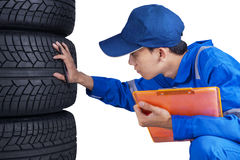 Technician with blue uniform checks tires. Portrait of of young technician working with a blue uniform and check a stack of tires Royalty Free Stock Photography