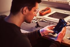 Technician carefully examines the integrity of the internal elements of the smartphone in a modern repair shop. The technician carefully examines the integrity stock photo