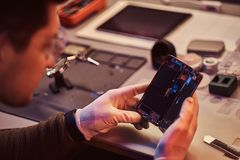 Technician carefully examines the integrity of the internal elements of the smartphone in a modern repair shop. The technician carefully examines the integrity royalty free stock photography
