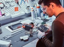Technician carefully examines the integrity of the internal elements of the smartphone in a modern repair shop. The technician carefully examines the integrity royalty free stock image