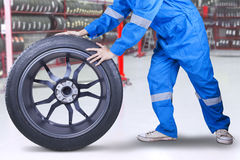 Technician changing a tire at workshop Royalty Free Stock Photos