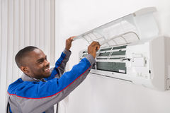 Technician Checking Air Conditioner. Happy Male Technician Checking Air Conditioner At Home stock photography