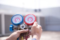 Technician is checking air conditioner ,measuring equipment for filling air conditioners royalty free stock photos