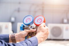 Technician is checking air conditioner ,measuring equipment for filling air conditioners royalty free stock photography