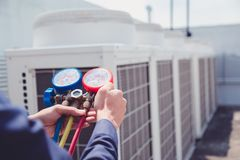 Technician is checking air conditioner ,measuring equipment for filling air conditioners royalty free stock image