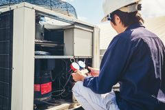 Technician is checking air conditioner.  royalty free stock images