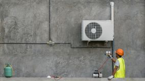 Technician is checking air conditioner. Technician is checking outdoor air conditioner unit stock photos