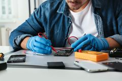 Technician checking broken smartphone at table in repair shop. Closeup royalty free stock image