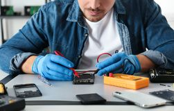 Technician checking broken smartphone at table in repair shop. Closeup royalty free stock photography