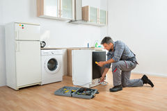Technician Checking Dishwasher With Digital Multimeter Royalty Free Stock Photography