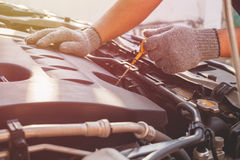 Technician checking or fixing engine of modern car. Hand of technician checking or fixing engine of modern car Royalty Free Stock Image