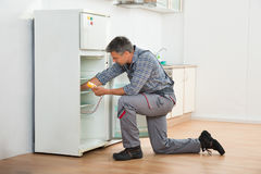 Technician Checking Fridge With Digital Multimeter. Mature male technician checking fridge with digital multimeter at home Royalty Free Stock Image