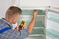 Technician Checking Fridge With Multimeter. Young Male Technician Checking Fridge With Digital Multimeter Stock Images