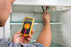Technician Checking Fridge With Multimeter. Young Male Technician Checking Fridge With Digital Multimeter Royalty Free Stock Image