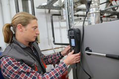 Technician checking installations with electronical device. Technician checking heat pump intensity with electronic device Royalty Free Stock Photo